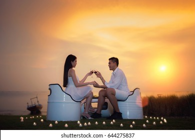 Asian boyfriend and girlfriend take diner with romantic sea, beach, candle and sunset in valentines day in tropical resort