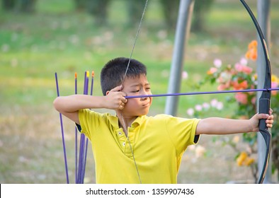 Asian boys are archery in camp adventure.