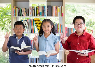 Asian boys and Asian girl are standing in front of bookshelf and reading book together with two fingers up all