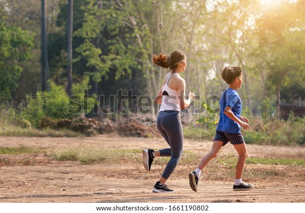 Asian Boys and Girls Fitness Outdoor Concept Selective boy running with a woman's hand as a jogging trainer Running is a sport that helps the athlete's body be strong.