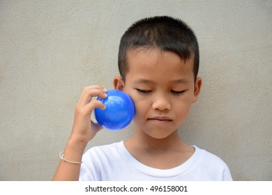 Asian boys play toy ball.Cement gray background