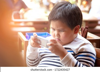 Asian boys playing games from mobile phones while traveling with family. Fat boy in white shirt playing smartphone in the restuarant.