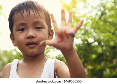 Asian boys show colored hands after playing coloring