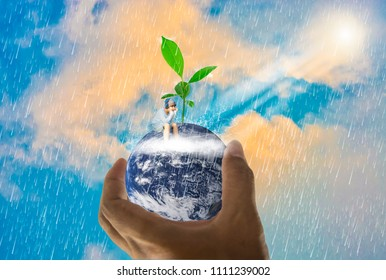 Asian boys sit on earth, in a handful, tree growing on top,With bright sky ิbackground and rain,Abstract concept  global warming worldwide,Elements of this image furnished by NASA (photo manipulation)