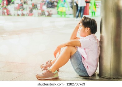 Asian boys sit stress and bad mood alone in the open space of the school, the concept of being bullied Cynicism and racism
