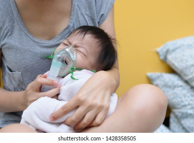 Asian boys are suffering from respiratory diseases and require treatment with spraying through the nose by inhalation mask.