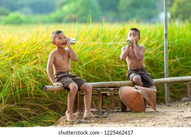 Asian boys talking on a can phone, Rural children communicate with the phone.