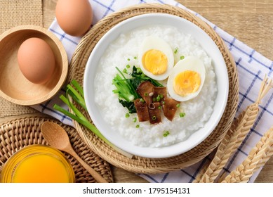 Asian breakfast food, Rice soup with boiled egg, grilled mushroom and spinach in bowl