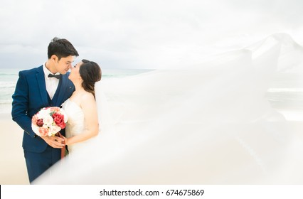 Asian bride and groom kissing on the summer beach.Bride and groom on a romantic moment on the sunset beach.