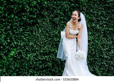Asian Bride She stood there laughing happy on her wedding day in the green garden.
