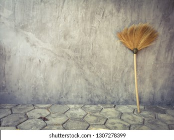 Asian broom on grey bricks is leaning against a grey skim coat painted wall.