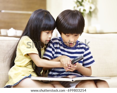 asian brother and sister sitting on sofa at home using a magnifying glass on a book.