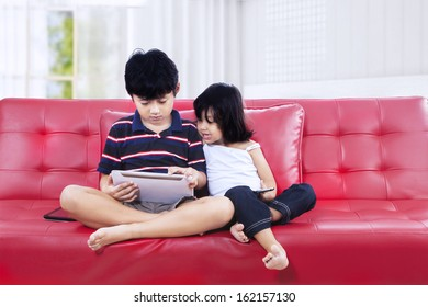 Asian brother and sister using a tablet computer on the couch