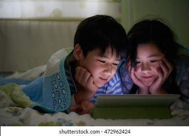Asian brother and sister watching cartoons on digital tablet