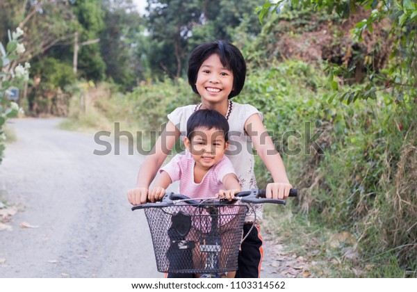 Asian brothers and sisters cycling in the park.