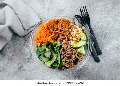 Asian buddha bowl on gray concrete table background. Grilled beef, carrot, cucumber, sprouted mung bean, topinambour noodles, mushrooms, sesame seeds, asian sause. Top view, copy space.