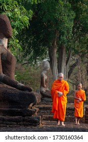 Asian Buddhist monk and novice meditation in front of the Buddha statue at the old temple