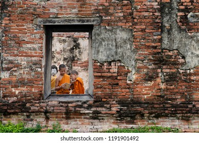 Asian buddhist novice monk is reading the holy book in the historical temple.