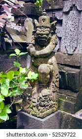 Asian Buddhist statue of an evil dragon god stands among the plants
