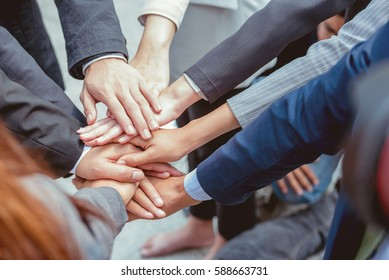Asian business employees hug hand together. Employees teamwork is importance for work.Cooperating together on various tasks reduces workloads for all employees.