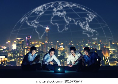 Asian business group in casual suits using smartphone, tablet and laptop for working or playing social networks and website on high-rise rooftop sites. Business and technology concept.