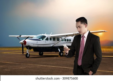 Asian business man calling with his cellphone with plane background