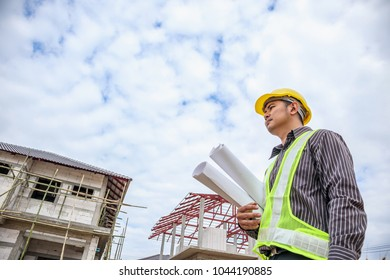 Asian business man construction engineer worker in protective helmet and blueprints paper on hand at house building site