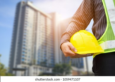 Asian business man construction engineer or architect worker with yellow protective helmet at large condominium building site