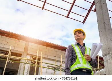 Asian business man construction engineer worker in protective helmet and blueprints paper on hand at building site