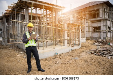 Asian business man construction manager and engineer worker in protective helmet hold blueprints paper on hand using tablet computer at building site