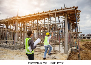 Asian business man construction manager and engineer worker in protective helmet hold blueprints paper on hand at building site