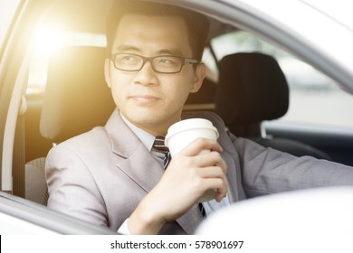 Asian business man drinking coffee while driving the car, in a morning with beautiful sunlight.