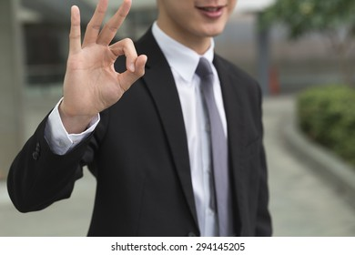 Asian business man give you an okay gesture.