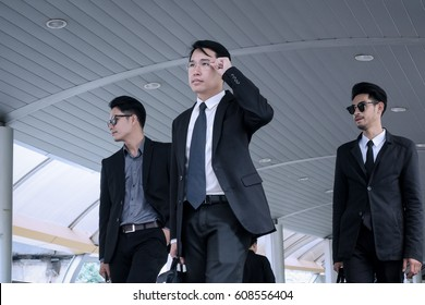 Asian business man with group of bodyguard walking on business street and looking away for safety and protection concept