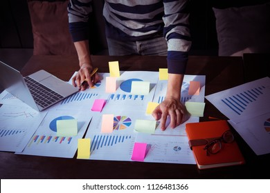 Asian business man hand holding note paper meeting with new startup project use post it notes to share idea discussion and analysis data charts and graphs.Business finances and accounting concept