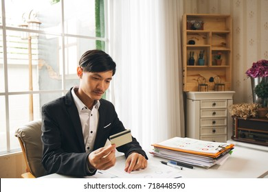 Asian business man in modern office with blank credit card in his hand and windows background at behind.