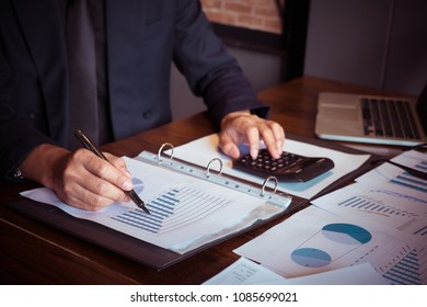 asian business man with new startup project hand pointing graph discussion and analysis data charts and graphs and using a calculator to calculate  numbers.Business finances and accounting con