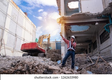 Asian business man pointing finger and talking walkie talkie, standing on the pile of bricks over large jackhammer construction vehicle machine