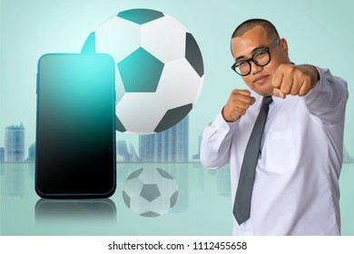 Asian business man punching with smart phone on city blurry background with football tournament 2018 