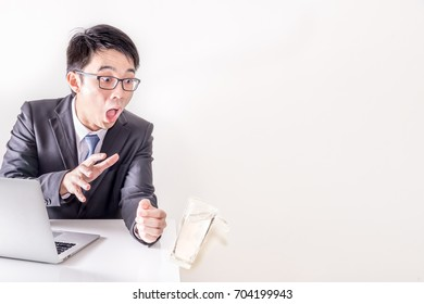 Asian business man shock because hand wipe the glass, water splash from glass before fall. when he working online in the office, Man  with notebook on table , free space at right si