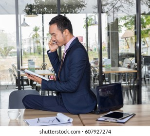 asian business man sitting on desk talking on mobile phone in a cafe