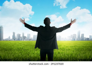 Asian business man standing on green meadow facing city. Business vision  concept