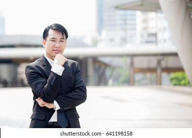 Asian Business man standing at outdoor place, portrait business conceptม 30-40 year old.