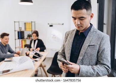 Asian business man talking on mobile phone in modern loft office