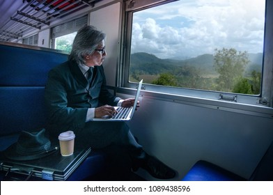 Asian business man thinking ideas strategy working concept in train near window, Man wearing suit with laptop computer