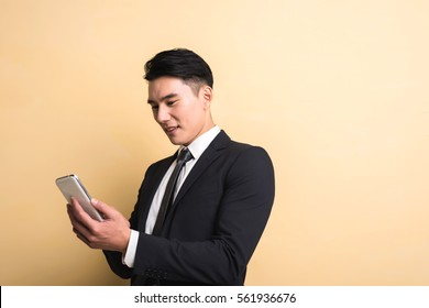 Asian business man use smart phone, closeup portrait on studio yellow background