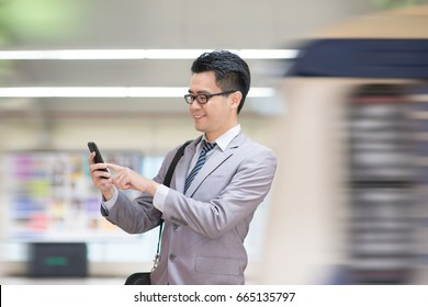 Asian business man using smart phone in subway station, train passing by at the background.