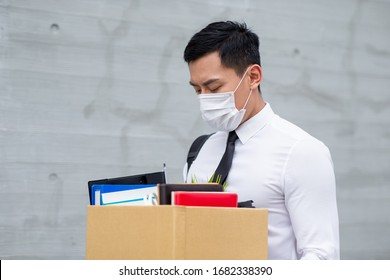 Asian business man wear face mask and he is being fired because of economic downturn due to the covid-19 spread all over the world