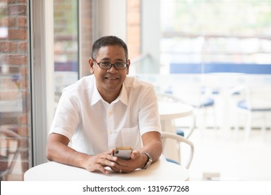 Asian business man wear white casual shirt relaxing in cafe use  smart phone for on line business communication or on line banking. successful business concept- Image