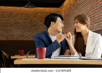 Asian business man and Asian business woman look at each other and Pinky swear with copy space on left side